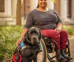 Photo of Anjali with red pants and black top with black lab Kolton by side.